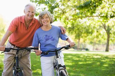 Older man and woman riding bikes in park