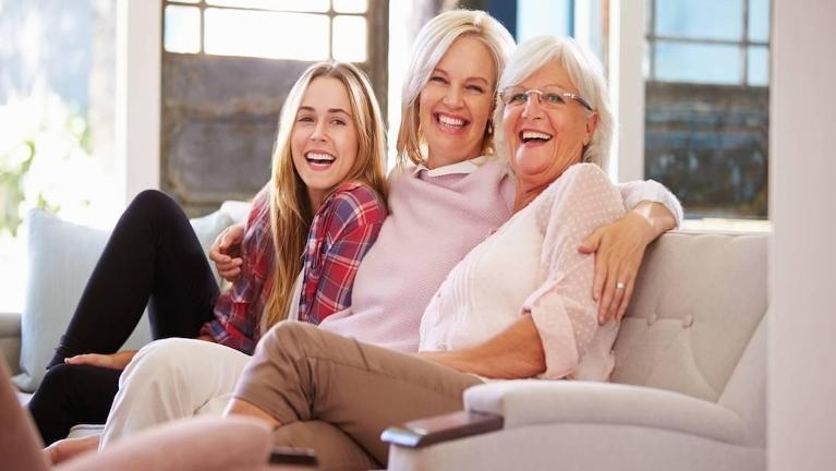 Daughter, mom, and grandma smiling on couch